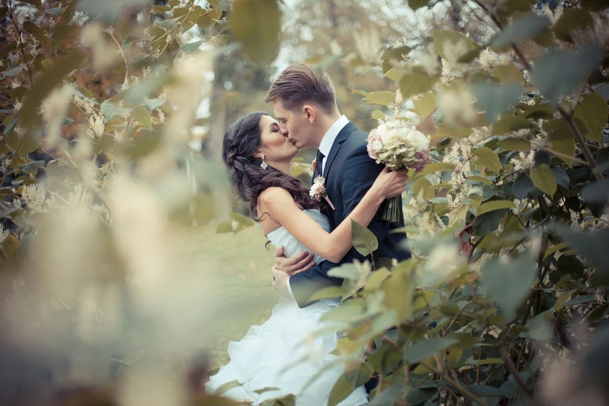 A Bride and Groom embrace in a garden symbolizing the Bride of Christ and our relationship with Christ